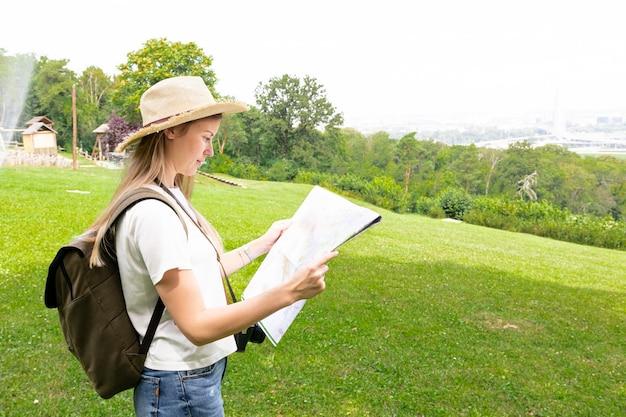 Vrouw die op gras op een kaart kijkt
