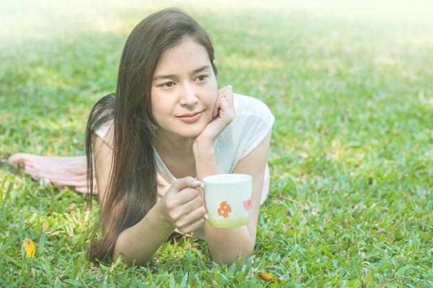 Vrouw die op grasgebied ligt met een kop van koffie in het park