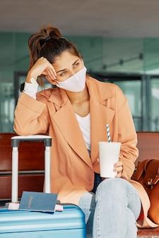 Vrouw die op haar bagage rust tijdens het dragen van een medisch masker op de luchthaven tijdens een pandemie