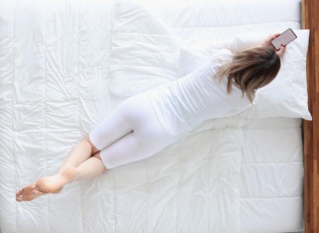 Vrouw die op haar buik in bed ligt en de mening van het telefoontip bekijkt. slapeloosheid concept