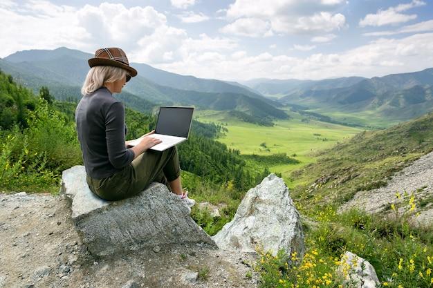Vrouw die op haar computer op de top van de berg werkt.