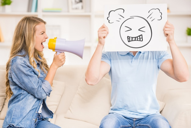 Vrouw die op haar echtgenoot met mondstuk schreeuwt.