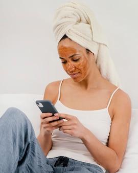 Vrouw die op haar gezichtsmasker wacht om zijn effect te maken