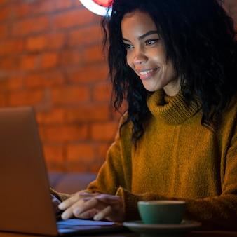 Vrouw die op haar laptop in een coffeeshop werkt