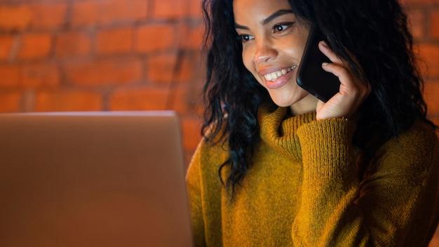 Vrouw die op haar laptop werkt tijdens het gesprek aan de telefoon
