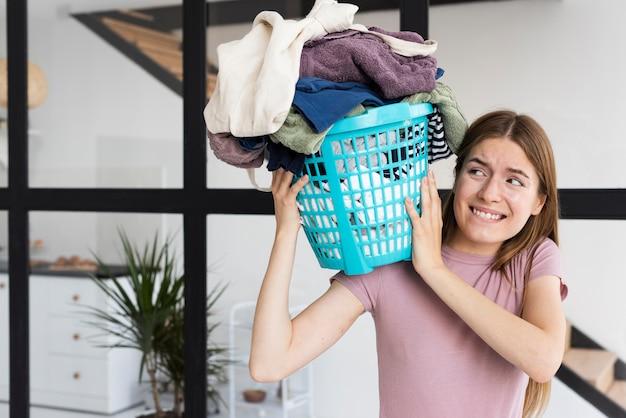 Vrouw die op haar schouder een mandhoogtepunt van kleren houdt