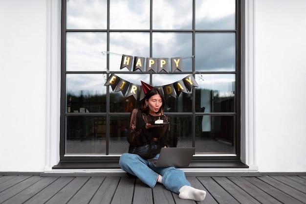 Vrouw die op haar verjaardag een videogesprek voert met haar familie