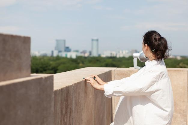 Vrouw die op het dak van de toren staat en geniet van de zomervakantie en kijkt naar panoramisch uitzicht