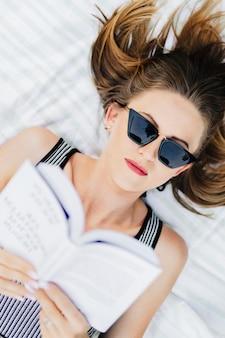 Vrouw die op het gras ligt en een boek leest