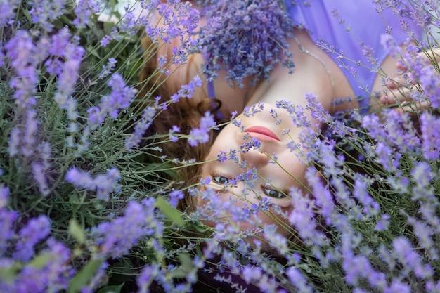 Vrouw die op het gras op een gebied van lavendel ligt