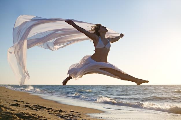 Vrouw die op het overzeese strand springt