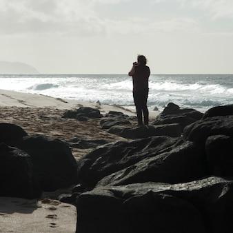 Vrouw die op het strand, haleiwa, het noordenkust fotograferen, oahu, hawaï, de vs