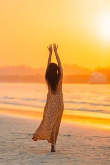 Vrouw die op het strand legt dat van de zomervakantie geniet die het overzees bekijkt