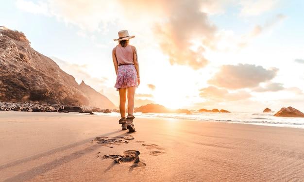 Vrouw die op het strand loopt dat van zonsondergang geniet