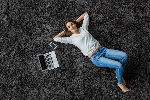 Vrouw die op het tapijt legt