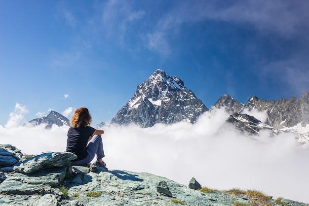 Vrouw die op hoge bergbovenkant rusten, die majestueuze de bergpiek bekijken van het menings dramatische landschap over de wolken, duidelijke blauwe hemel.