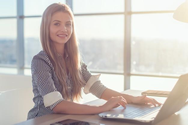 Vrouw die op kantoor aan huis hand op toetsenbord werkt.
