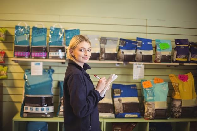 Vrouw die op kladblok in winkel schrijft