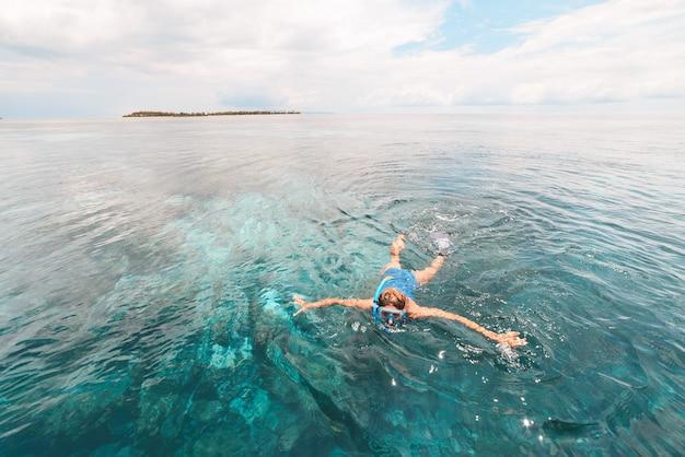 Vrouw die op koraalrif tropische caraïbische overzees snorkelt