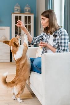 Vrouw die op laag haar hond een traktatie geeft