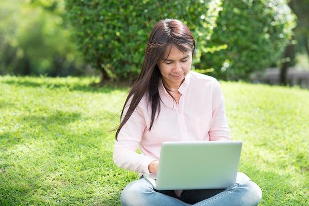 Vrouw die op laptop buiten in het park werkt