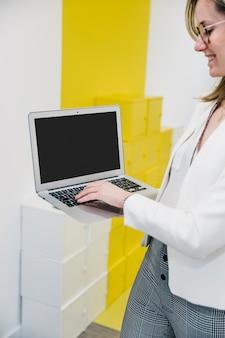 Vrouw die op laptop en het glimlachen typen