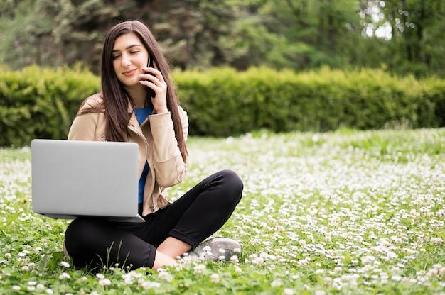 Vrouw die op laptop in de natuur werkt