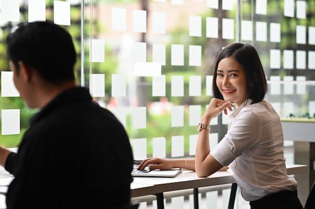 Vrouw die op laptop in mede werkruimte werkt met portretschot dat camera bekijkt.