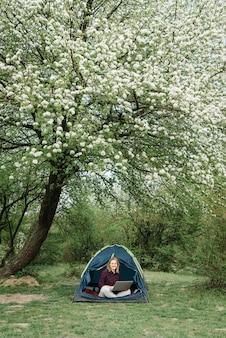 Vrouw die op laptop in tent in aard werkt. jonge freelancer zitten in het kamp. ontspannen op camping in bos, weide. werken op afstand, buitenactiviteiten in de zomer. gelukkig meisje ontspannen, werken op vakantie.