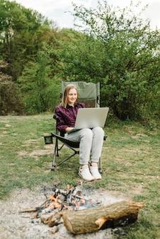 Vrouw die op laptop online aan aard werkt. jonge freelancer ontspannen in het bos. werken op afstand, buitenactiviteiten in de zomer. reizen, wandelen, technologie, toerisme, mensenconcept.