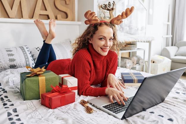 Vrouw die op laptop op nieuwjaar werkt