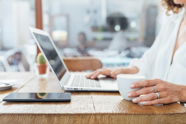 Vrouw die op laptop schrijft terwijl het drinken van koffie in een bar. freelance concept werknemer.