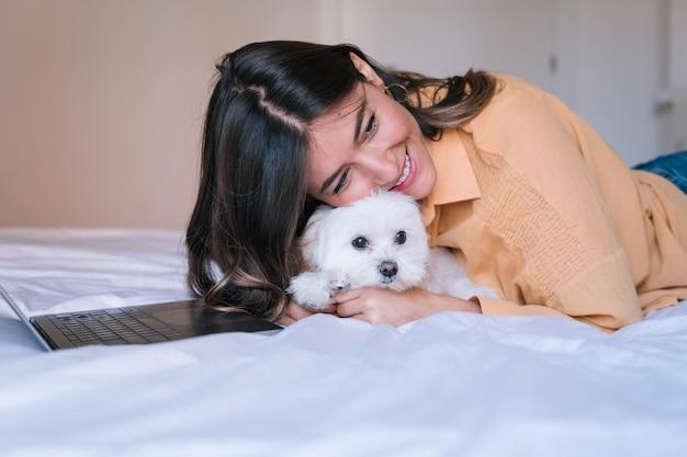 Vrouw die op laptop thuis werkt. leuke maltese hond bovendien