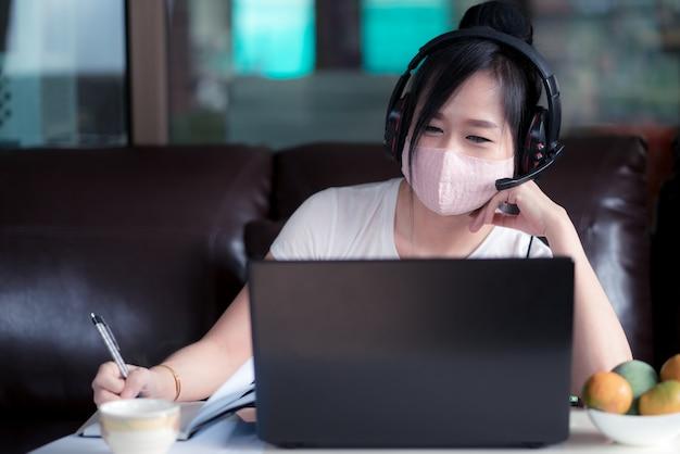 Vrouw die op laptop thuis werkt met een gezichtsmasker voor bescherming ter bescherming van 2019 - ncov, covid 19 of coronavirus. wfh of working from home concept.