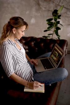 Vrouw die op laptop werkt en aantekeningen maakt