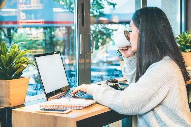 Vrouw die op laptop werkt en tegelijkertijd koffie drinkt