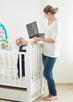 Vrouw die op laptop werkt en voor haar baby zorgt