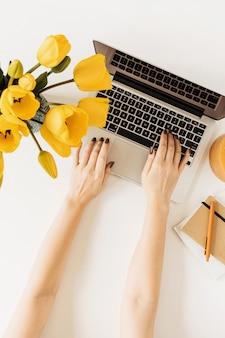 Vrouw die op laptop werkt. kantoor aan huis bureau werkruimte met laptop, tulp bloemen boeket op wit