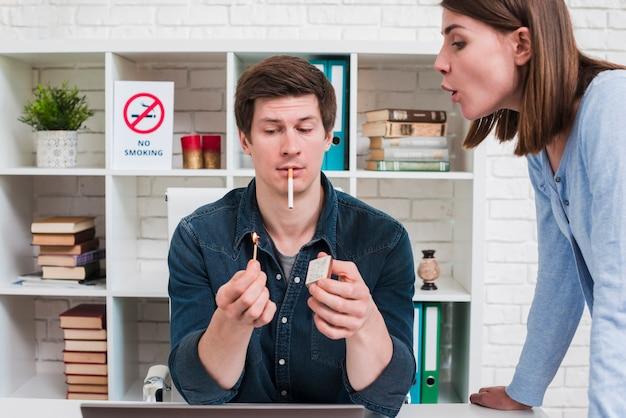 Vrouw die op matchstickgreep door haar vriend voor het aansteken van de sigaret blaast