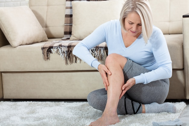 Vrouw die op middelbare leeftijd aan pijn in been thuis lijdt.