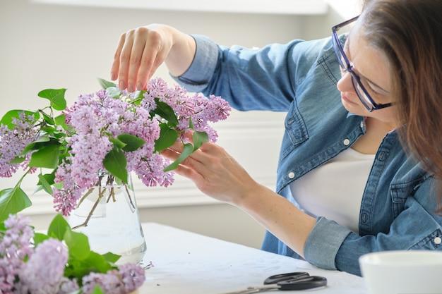 Vrouw die op middelbare leeftijd boeket van lilac takken maakt