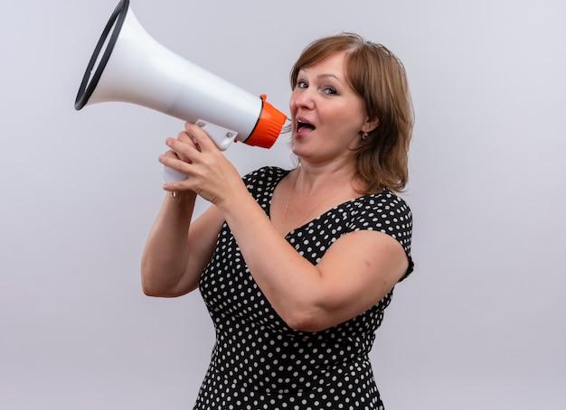 Vrouw die op middelbare leeftijd door spreker op geïsoleerde witte muur spreekt