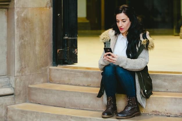 Vrouw die op middelbare leeftijd een vraag op haar celtelefoon in de straat beantwoordt.