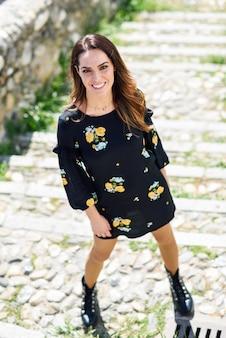 Vrouw die op middelbare leeftijd gebloeide kleding in stedelijke stappen draagt.