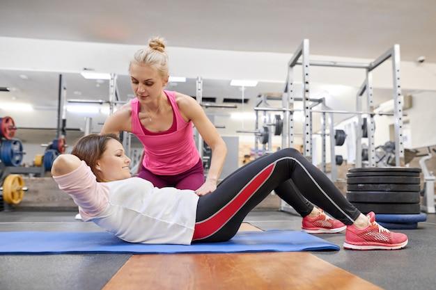 Vrouw die op middelbare leeftijd sportenoefening in fitness centrum doet.