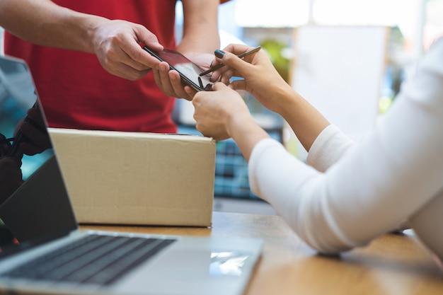 Vrouw die op mobiel ondertekenen om pakket van de leveringsmens te krijgen.