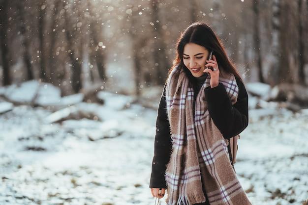 Vrouw die op mobiele telefoon in koude de winterdag spreekt.