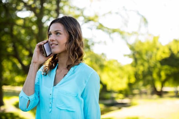 Vrouw die op mobiele telefoon in park spreekt