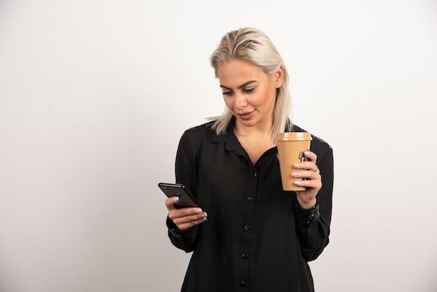 Vrouw die op mobiele telefoon kijkt en een kop van koffie houdt. hoge kwaliteit foto