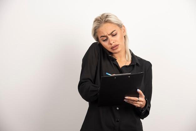 Vrouw die op mobiele telefoon spreekt en een klembord houdt. hoge kwaliteit foto